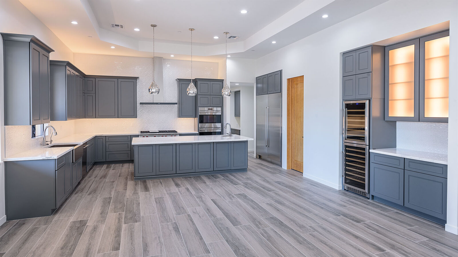 A wide kitchen with grey-painted panels