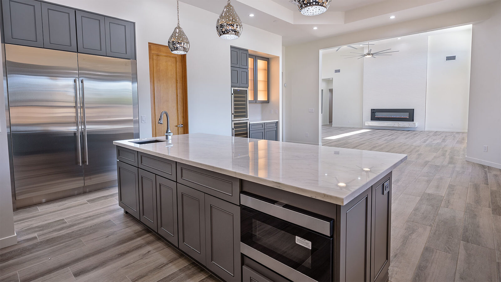 A kitchen island with a white marbled surface and a grey foundation